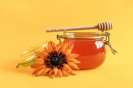 Glass jar of natural honey with wooden drizzler and rudbeckia flower on yellow background. 版權商用圖片