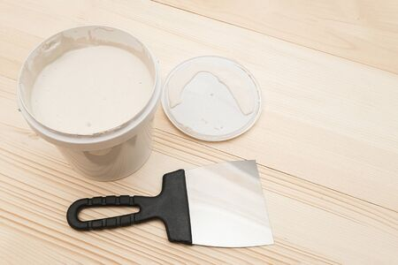 Spatula and a bucket of white putty on wooden boards with copy space.