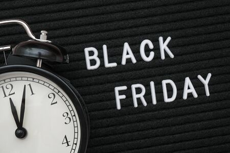 White text Black friday on black letter board and alarm clock, closeup. Concept Black friday , season sales time. Flat lay Top view Copy space Template layout for your design.
