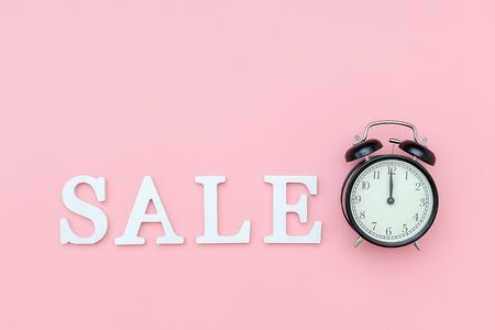 Black alarm clock and text Sale from white volume letters on a pink background. Concept Black friday , sales time. Flat lay Top view Copy space Template for design. Stock Photo