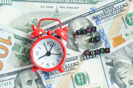 Time is money text and red alarm clock on background of American hundreds dollar bills, closeup. Creative concept quote of the day. Top view Flat lay Copy space.