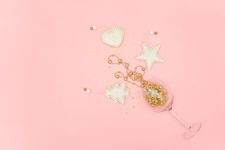Wine glass poured out golden christmas decoration and confetti stars on pink background. New Year, Christmas, Holiday concept Minimal style Top view Flat lay Copy space Greeting card, invitation.