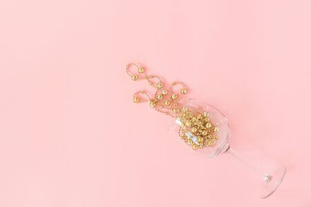 Wine glass poured out golden christmas decoration garland baubles on pink background. New Year, Christmas, Holiday concept Minimal style Top view Flat lay Copy space Greeting card, invitation.