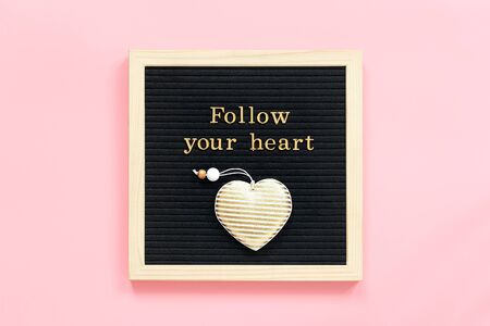 Follow your heart. Motivational quote in gold letters and decorative textile heart on black letter board on pink background. Top view Flat lay Concept inspirational quote of the day. Reklamní fotografie
