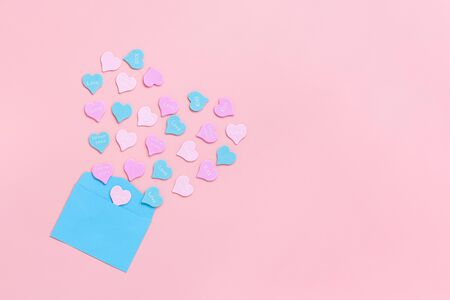 Colorful hearts with text LOVE, KISS, FOREVER YOURS fly out in the form of heart from blue paper envelope on pink background . Valentines day concept. Gift for lover. love confession Copy space.