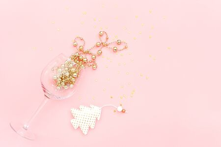 Wine glass poured out golden decoration, christmas tree and confetti stars on pink background. New Year and Christmas concept Minimal style Top view Flat lay Copy space Greeting card, invitation. Stock fotó