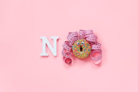 Funny face of woman from donut with eyes and hair from centimeter tape on plate and text no on pink background. Concept diet and abandonment of dounuts, fast food, unhealthy food.