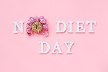 Text No diet day and abstract funny face of woman from donut with eyes and hair from centimeter tape on plate on pink background. Concept International No Diet Day, 6 may Top view Flat lay. Фото со стока