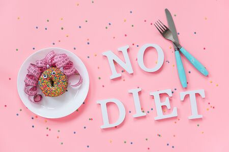 Abstract funny face of woman from donut with eyes and hair from centimeter tape on plate, cutlery and text No diet on pink background. Concept International No Diet Day, 6 may Top view Flat lay.