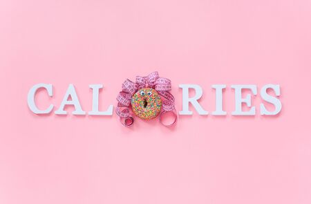 Text calories from volume letters and abstract funny face of woman from donut with eyes and hair from centimeter tape on pink background. Diet or unhealthy food concept Top view Flat lay Copy space.