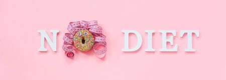 Text No diet and abstract funny face of woman from donut with eyes and hair from centimeter tape on plate on pink background. Concept International No Diet Day, 6 may Top view Flat lay Banner.