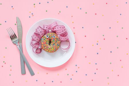 Abstract funny face of woman from donut with eyes and hair from centimeter tape on plate, cutlery on pink background. Diet or unhealthy food concept Top view Flat lay Copy space.