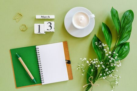 Wooden cubes calendar March 13. Notepad, cup of coffee, bouquet flowers on green background. Concept hello spring Creative Top view Flat lay Mock up.