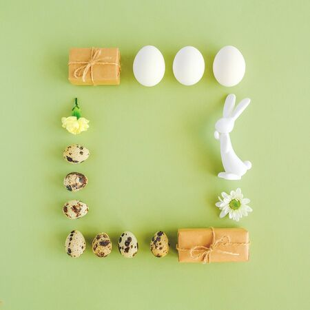 Happy easter festive square frame. Easter layout made of various eggs, bunny figurine, flowers and craft gift on green background with copy space Creative Flat lay Top view. Reklamní fotografie