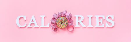 Text calories from white letters and abstract funny woman made donut with eyes and hair from centimeter tape on pink background. Diet or unhealthy food creative concept Top view Flat lay Banner.