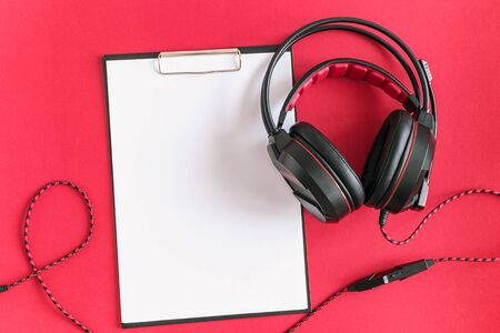 Black headphones and clipboard notepad with white blank paper on red background. Concept listening to audio material and abstract, distance education. Top view copy space.