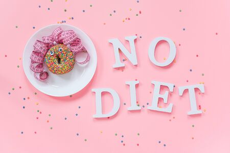 Abstract funny face of woman from donut with eyes and hair from centimeter tape on plate and text No diet on pink background. Concept International No Diet Day, 6 may Top view Flat lay. Фото со стока