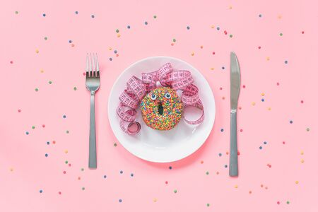 Abstract funny face of woman made donut with eyes and hair from centimeter tape on plate, cutlery on pink background. Fast food, fattening and unhealthy eating creativity concept Top view.