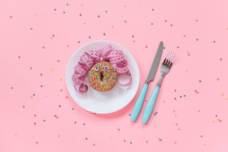 Abstract funny face of woman from donut with eyes and hair from centimeter tape on plate and cutlery on pink background. Concept International No Diet Day, 6 may Top view Flat lay Copy space.