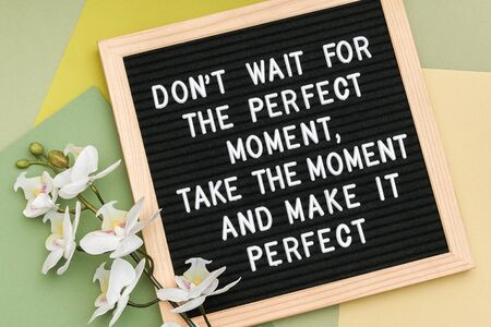 N'attendez pas le moment parfait, prenez le moment et rendez-le parfait. Citation de motivation sur le cadre du tableau à lettres et l'orchidée fleurie sur fond vert. Citation inspirante de concept. Banque d'images