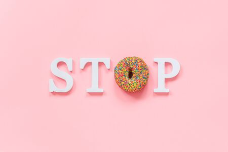 Text STOP from white volume letters and glazed colorful donut on pink background. Diet, refusal of fast food, unhealthy food Top view Flat lay Copy space.