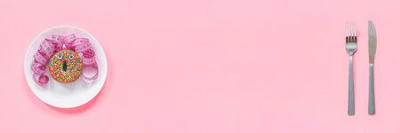 Abstract funny face of woman made donut with eyes and hair from centimeter tape on plate, cutlery on pink background. Fast food, fattening and unhealthy eating creativity concept Banner Copy space.