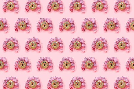 Donat pattern on pink background. Abstract funny face of woman from donut with eyes and hair from centimeter tape. Diet or unhealthy food concept Top view Flat lay.