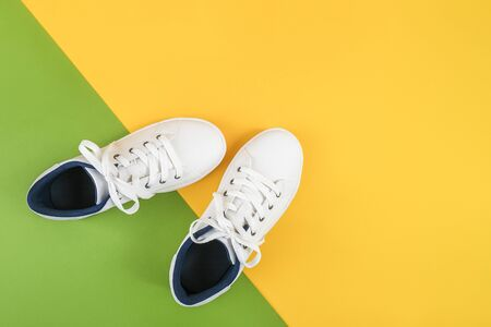 White sports shoes, sneakers with shoelaces on a green and yellow background. Sport lifestyle concept Top view Flat lay.