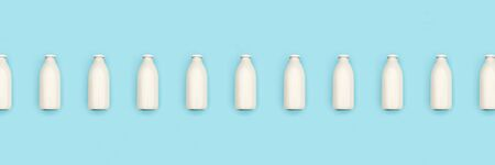 Glass bottles of milk in a row on blue background. Flat lay Top view Banner Copy space.