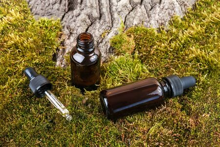 Two brown glass bottles and pipette whith serum, essential oil on green moss and tree bark background. Natural Organic Spa Cosmetic concept.