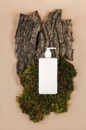 Cream, moisturizing lotion, shampoo or other cosmetic product in white blank bottle with dispenser on green moss and tree bark background. Natural Organic Spa Cosmetic concept Top view. Stock Photo