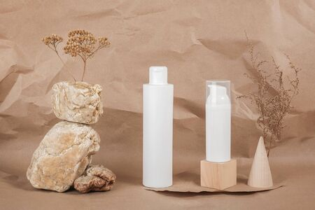 Two white blank cosmetic tube with cream, lotion or shampoo, stones, geometric shape, dried plant flowers on beige craft paper background. Natural Organic Spa Cosmetic.