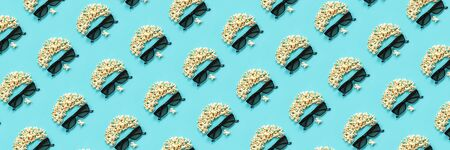 Pattern made with abstract image of viewer, 3D glasses and popcorn on blue background. Creative concept cinema movie and entertainment Flat lay Top view. Standard-Bild