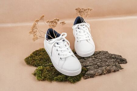 Ethical vegan shoes concept. A pair of white sneakers with dry flowers on tree bark and moss, neutral beige craft paper background.