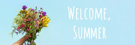 Welcome summer text. Female hand holds bright colorful bouquet of wild flowers against blue sky. Hello summer concept.