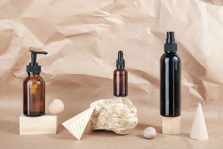 Brown glass bottles of cosmetic products on stone, wooden geometric shapes on beige paper background. Natural Organic Spa Cosmetic Beauty concept Front view Mockup.