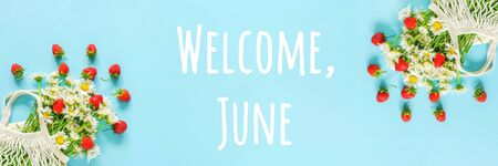 Welcome June text. Bouquet of white chamomile in reusable shopping eco mesh bag and splash red strawberries on blue background. Concept Hello summer. Banner Top view. Standard-Bild