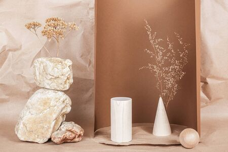 Creative podium for cosmetics or you merchandise, products. Layout made of from wooden geometric shapes, stones and dried flowers on brown beige paper background. Standard-Bild