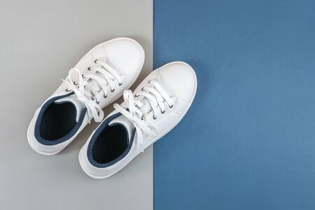 White sports shoes, sneakers with shoelaces on grey blue background. Sport lifestyle concept Top view Flat lay Copy space. Standard-Bild