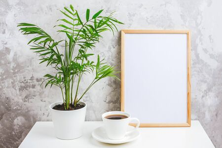 Wooden vertical frame with white blank card, cup of coffee and green exotic palm flower in pot on table on gray concrete wall background. Mockup Template for your design, text.