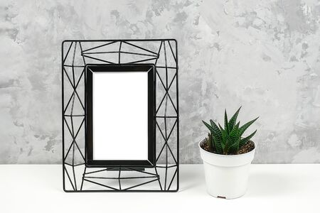Black metal vertical frame with white blank and succulent flower on table against grey concrete wall. Mockup Template for your design, text.