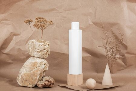 One white blank cosmetic tube with cream, lotion or shampoo, stones, geometric shape, dried plant flowers on beige craft paper background. Natural Organic Spa Cosmetic.
