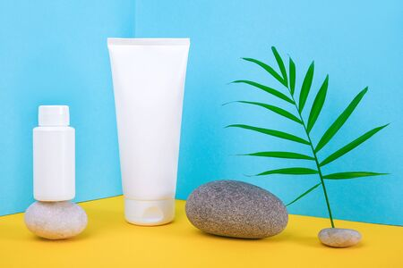 White blank cosmetics bottles, tube of cream, lotion for body, face, hand or other cosmetic product and gray rocks, palm leaf on blue yellow background. Mockup Front view, Corner composition .