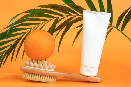 White blank cosmetic tube of cream or body lotion, orange fruit, wooden anti-cellulite massager and green branch palm. Concept fight against cellulite. Mockup Front view.