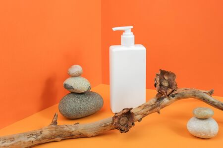 One white blank cosmetic bottle with dispenser, rocks, wooden stick with dried flowers in corner space on orange background. Mockup Front view Copy space. Standard-Bild