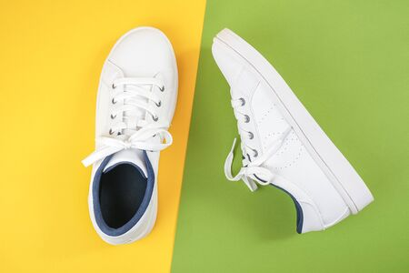 White sports shoes, sneakers with shoelaces on a green and yellow background. Sport lifestyle concept Top view Flat lay Copy space. Standard-Bild