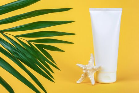 White blank cosmetic tube with sunscreen, suncream for face or body, starfish and green brunch palm on yellow background. Concept skin care in summer holiday Mockup Front view Copy space. Standard-Bild