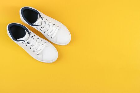 White sports shoes, sneakers with shoelaces on a yellow background. Sport lifestyle concept Top view Flat lay Copy space. Standard-Bild