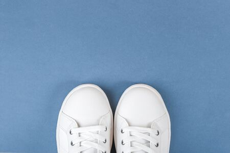 White sports shoes, sneakers with shoelaces on blue background. Sport lifestyle concept Top view Flat lay Copy space.