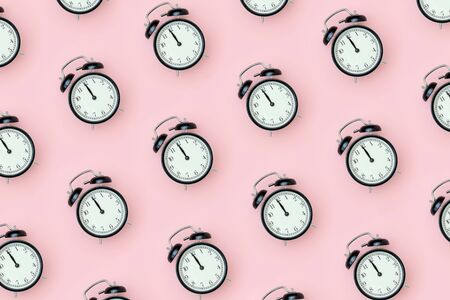 Pattern with black alarm clock on pink background. Minimal style Top view Template for your text, design.